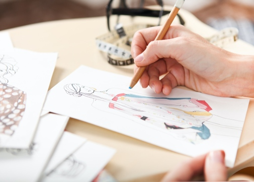 Dressmaker is drawing a fashion sketch. Photo: Daria Petrenko © Mostphotos